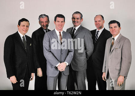 1960s SIX BUSINESSMEN EXECUTIVE GROUP ALL CAUCASIAN WEARING SUITS STANDING IN LINE SMILING LOOKING AT CAMERA  - kc3873 HAR001 HARS SATISFACTION STUDIO SHOT HEALTHINESS 6 MANAGER COPY SPACE FRIENDSHIP HALF-LENGTH PERSONS MALES SIX CORPORATE CONFIDENCE EXECUTIVES EXPRESSIONS MIDDLE-AGED MIDDLE-AGED MAN EYE CONTACT SUCCESS SUIT AND TIE SELLING HAPPINESS CHEERFUL STRENGTH STYLES POWERFUL PRIDE AUTHORITY OCCUPATIONS SMILES BOARD OF DIRECTORS BOSSES CONNECTION JOYFUL STYLISH VARIOUS FASHIONS MANAGERS MID-ADULT MID-ADULT MAN SALESMEN TOGETHERNESS CAUCASIAN ETHNICITY HAR001 OLD FASHIONED - Stock Photo
