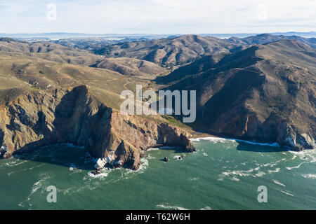 Seen from an aerial perspective, the cold waters of the Pacific Ocean wash against the rocky Northern California coastline in Marin. - Stock Photo
