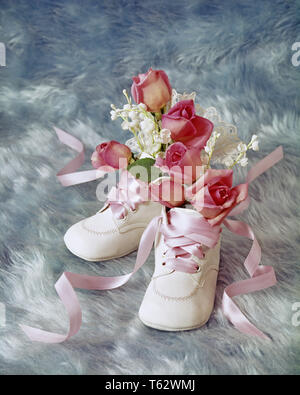1970s 1980s BIRTHDAY STILL LIFE OF WHITE BABY SHOES HOLDING MINIATURE PINK ROSES AND BABY'S BREATH FLOWERS ON BLUE BACKGROUND - kf8897 PHT001 HARS OLD FASHIONED - Stock Photo