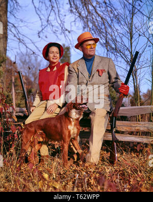 1960s EXPERIENCED COUPLE DRESSED FOR UPLAND GAME BIRD HUNTING HOLDING SHOTGUNS SITTING ON RAIL FENCE BESIDE IRISH SETTER DOG  - kg2769 HAR001 HARS HUNTING OLD TIME NOSTALGIA OLD FASHION 1 FACIAL STYLE SAFETY TEAMWORK GUNS VACATION ATHLETE RELAXING JOY LIFESTYLE FEMALES MARRIED RURAL SPOUSE HUSBANDS HEALTHINESS COPY SPACE FULL-LENGTH LADIES PHYSICAL FITNESS PERSONS MALES ATHLETIC CONFIDENCE EXPRESSIONS MIDDLE-AGED PARTNER MIDDLE-AGED MAN SUCCESS TIME OFF SKILL ACTIVITY AMUSEMENT SPORTING HAPPINESS MAMMALS WELLNESS ADVENTURE HOBBY LEISURE STRENGTH STYLES TRIP INTEREST GETAWAY EXPERIENCED CANINES - Stock Photo