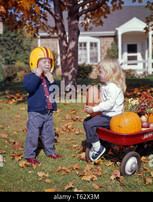 1960s LITTLE BOY PUTTING ON FOOTBALL HELMET AND SMILING BLOND GIRL SITTING IN RED WAGON HOLDING FOOTBALL - kh1749 HAR001 HARS PLASTIC YELLOW COLOR OLD TIME BUSY NOSTALGIA BROTHER OLD FASHION SISTER 1 PUTTING WAGON JUVENILE YARD BLOND SAFETY TEAMWORK COMPETITION ATHLETE LIFESTYLE FEMALES HOUSES BROTHERS HEALTHINESS HOME LIFE NATURE COPY SPACE FRIENDSHIP FULL-LENGTH INSPIRATION RESIDENTIAL CARING MALES RISK ATHLETIC BUILDINGS SIBLINGS SISTERS HAPPINESS AND EXCITEMENT FALL SEASON PRIDE IN ON HOMES SIBLING CONNECTION CONCEPTUAL RESIDENCE STYLISH SUPPORT GROWTH JUVENILES SEASON TOGETHERNESS - Stock Photo