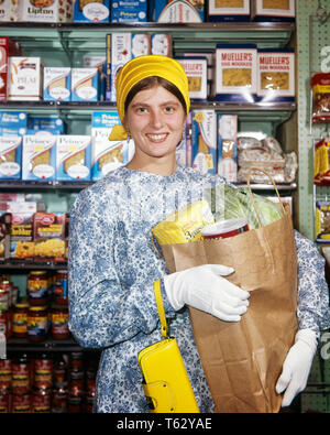 1960s SMILING WOMAN HOUSEWIFE HOLDING GROCERY BAG YELLOW PURSE WEARING BLUE PRINT DRESS YELLOW TURBAN HAT AND WHITE GLOVES - ks5430 LAW001 HARS PRINT 1 COMMUNICATION YOUNG ADULT WEAR PLEASED JOY LIFESTYLE SATISFACTION FEMALES GROWNUP HEALTHINESS HOME LIFE COPY SPACE HALF-LENGTH LADIES PERSONS GROWN-UP CARING CONFIDENCE SHOPPER EYE CONTACT HOMEMAKER SHOPPERS HAPPINESS HOMEMAKERS CHEERFUL AND HOUSEWIVES SMILES JOYFUL NOURISHMENT STYLISH TURBAN WHITE GLOVES YOUNG ADULT WOMAN CAUCASIAN ETHNICITY HEAD WARE OLD FASHIONED - Stock Photo