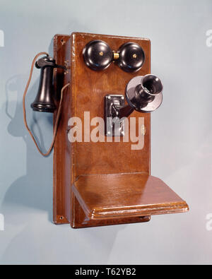 1910s 1920s 1930s ANTIQUE WOOD CASE CRANK WALL TELEPHONE DRY CELL BATTERY VERSION INVENTED 1907  - ks7595 HAR001 HARS INNOVATION BATTERY PHONES CONNECTION CONCEPTUAL STILL LIFE TELEPHONES STYLISH HAR001 OLD FASHIONED VERSION - Stock Photo