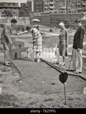 1920s 1930s TWO COUPLES PLAYING MINIATURE GOLF PHILADELPHIA PA USA  - o5377 HAR001 HARS YOUNG ADULT TEAMWORK COMPETITION ATHLETE JOY LIFESTYLE FEMALES MARRIED SPOUSE HUSBANDS LUXURY UNITED STATES FRIENDSHIP LADIES PERSONS UNITED STATES OF AMERICA MALES ATHLETIC B&W MINIATURE GOALS AMUSEMENT HAPPINESS LEISURE STYLES VICTORY EXCITEMENT PA RECREATION INNOVATION GOLF BALL CONNECTION STYLISH FASHIONS RELAXATION TOGETHERNESS WIVES YOUNG ADULT MAN YOUNG ADULT WOMAN BLACK AND WHITE CAUCASIAN ETHNICITY HAR001 OLD FASHIONED - Stock Photo