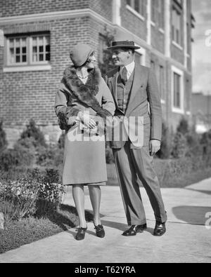 1920s SMILING COUPLE MAN WOMAN WALKING ARM IN ARM WOMAN WEARING COAT WITH FUR TRIM - p2488 HAR001 HARS LIFESTYLE FEMALES MARRIED SPOUSE HUSBANDS HEALTHINESS HOME LIFE COPY SPACE FRIENDSHIP FULL-LENGTH LADIES PERSONS MALES B&W SUIT AND TIE HAPPINESS STYLES CLOCHE TRIM CONNECTION STYLISH COOPERATION FASHIONS MID-ADULT MID-ADULT WOMAN TOGETHERNESS WIVES YOUNG ADULT WOMAN BLACK AND WHITE CAUCASIAN ETHNICITY HAR001 OLD FASHIONED - Stock Photo