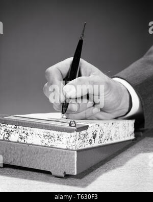 1950s 1960s MALE HAND HOLDING DESK PEN WRITING ON DAILY CALENDAR PAGE OR PAPER PAD - s13854 HAR001 HARS CONCEPTUAL STYLISH OR SYMBOLIC CONCEPTS BLACK AND WHITE CAUCASIAN ETHNICITY DAILY HANDS ONLY HAR001 OLD FASHIONED REPRESENTATION - Stock Photo