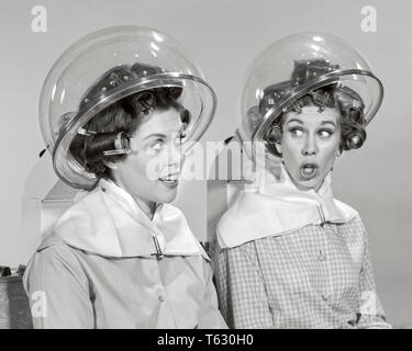 1960s Two women rollers curler in their hair sitting under hair salon dryers talking gossiping - s15079 HAR001 HARS SALON INFORMATION HOOD LIFESTYLE GROWNUPS FEMALES GOSSIP STUDIO SHOT GROWNUP COPY SPACE FRIENDSHIP HALF-LENGTH LADIES PERSONS GROWN-UP SPEAK PAIRS SIBLINGS CONFIDENCE SISTERS GOSSIPING B&W ROLLERS CURLERS HAPPINESS DISCOVERY LEISURE THEIR NETWORKING IN OPPORTUNITY SIBLING SMILES GOSSIPS CONNECTION CONCEPTUAL DRYERS HAIR DRYER BEAUTY PARLOR STYLISH CURLER PLASTIC DOME COOPERATION HAIR SALON MID-ADULT MID-ADULT WOMAN TOGETHERNESS YOUNG ADULT WOMAN BLACK AND WHITE - Stock Photo