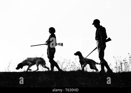 1920s 1930s ANONYMOUS SILHOUETTE MAN AND WOMAN HUNTERS CARRYING GUNS EACH WITH A HUNTING DOG  - s2541 HAR001 HARS LEISURE SILHOUETTED AND CANINES RECREATION POOCH CONNECTION ANONYMOUS CANINE COOPERATION FIREARM FIREARMS HUNTERS MAMMAL MID-ADULT MID-ADULT MAN MID-ADULT WOMAN TOGETHERNESS BLACK AND WHITE HAR001 OLD FASHIONED - Stock Photo