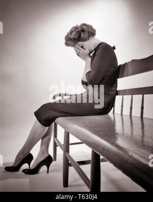 1950s SILHOUETTED DISTRAUGHT WOMAN SITTING ON BENCH CRYING HOLDING HANDS OVER FACE SADNESS DEPRESSION LOSS - s3493 HAR001 HARS LOW ANGLE POWERFUL MOOD SORROW EMBARRASSED GRIEVING CONCEPTUAL GLUM FAILURE MID-ADULT MID-ADULT WOMAN MISERABLE BLACK AND WHITE CAUCASIAN ETHNICITY HAR001 OLD FASHIONED - Stock Photo