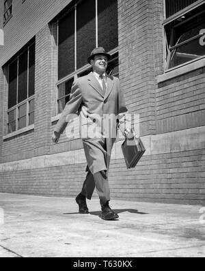 1950s 1960s BUSY SELF CONFIDENT SALESMAN WALKING BRISKLY DOWN CITY STREET WEARING TOP COAT HAT HOLDING BRIEFCASE SMILING - s7416 HAR001 HARS JOY LIFESTYLE SPEED SATISFACTION CELEBRATION HEALTHINESS COPY SPACE FULL-LENGTH PHYSICAL FITNESS PERSONS INSPIRATION CARING MALES CONFIDENCE EXPRESSIONS B&W SELF SUCCESS VISION SUIT AND TIE SELLING HAPPINESS CHEERFUL STRENGTH STRATEGY CUSTOMER SERVICE EXCITEMENT LEADERSHIP LOW ANGLE POWERFUL PROGRESS DIRECTION PRIDE OPPORTUNITY AUTHORITY OCCUPATIONS SMILES ANIMATED CONCEPTUAL JOYFUL STYLISH CONFIDENT MID-ADULT MID-ADULT MAN SALESMEN TOP COAT - Stock Photo