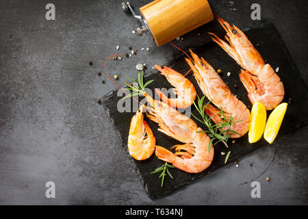 Seafood. Raw shrimps with spice and lemon on a slate board. Top view flat lay background. Free space for your text. - Stock Photo