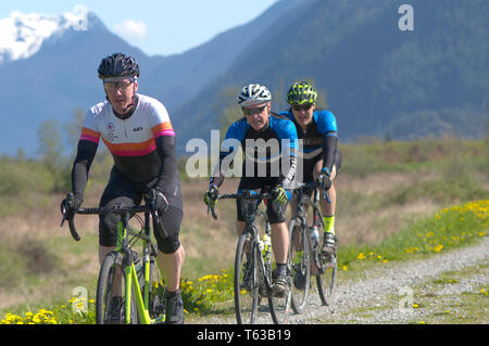 April 28, 2019 Rock the Ridge Volume 1 Cycling Competition  in Maple Ridge, British Columbia, Canada. Cyclists riding along a gravel dike. - Stock Photo