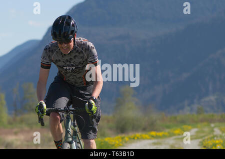 April 28, 2019 Rock the Ridge Volume 1 Cycling Competition in Maple Ridge, British Columbia, Canada. Cyclist riding along a gravel dike. - Stock Photo