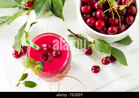 Cherry fruit Yogurt smoothie or milk shake in glass jar on a wooden table. Natural detox, fruit dessert, healthy dieting concept. - Stock Photo
