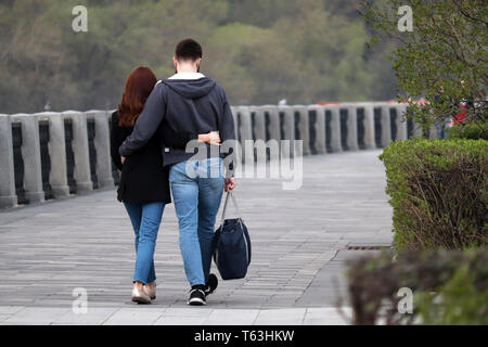Couple in love hugging and walking in a park, rear view. Embracing guy and girl on romantic date, people in jeans, relationship, real feelings