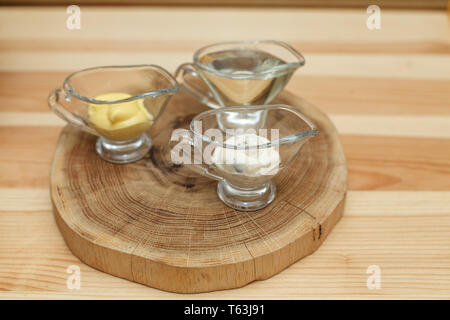 Set of three transparent sauceboats with different sauces on wooden plate - Stock Photo