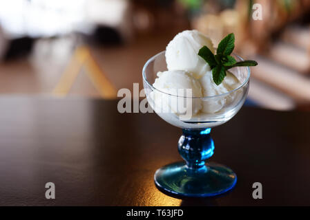 balls of dairy ice cream in a beautiful glass with a sprig of mint in a restaurant - Stock Photo