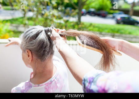 Young woman combs the hair of an old woman - Stock Photo