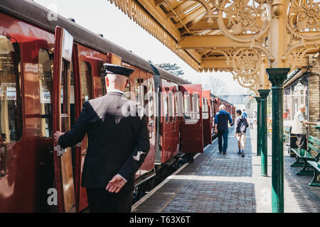 Sheringham, UK - April 21, 2019: Conductor in uniform closing a door of retro Poppy Line steam train at Sheringham station. Sheringham is an English s - Stock Photo