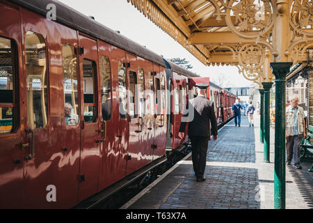 Sheringham, UK - April 21, 2019: Conductor in uniform walking past a retro Poppy Line steam train at Sheringham station. Sheringham is an English seas - Stock Photo