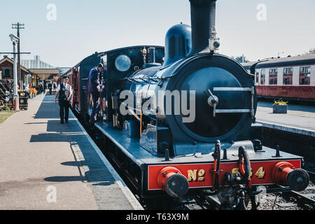 Sheringham, UK - April 21, 2019: Staff walking on platform next to The Poppy Line steam  train, also known as the North Norfolk Railway, a Heritage St - Stock Photo