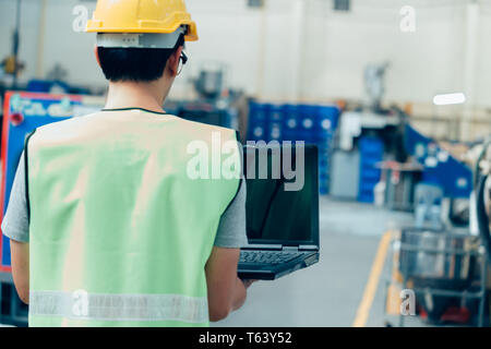 Asian male Industrial engineer in hardhat works with laptop in safety jacket at heavy industry factory. Processing plastic injection molding industry - Stock Photo