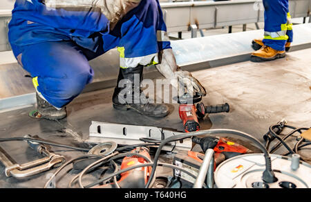 Worker using angle grinder on construction site. - Stock Photo