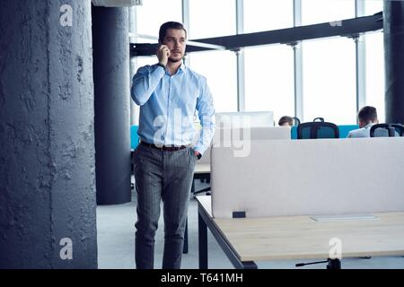Mature business man standing inside office building and using cell phone. - Stock Photo