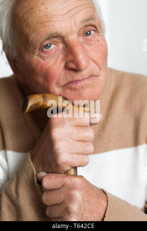Portrait of an old sad man who put his head on the handle of a wooden cane, the concept of loneliness at home. - Stock Photo