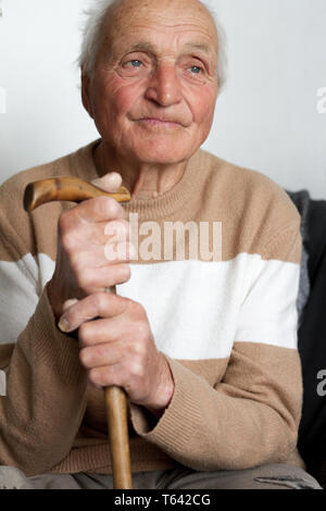 Portrait of a smiling old man who put his hands on the handle of a wooden cane, health at home.