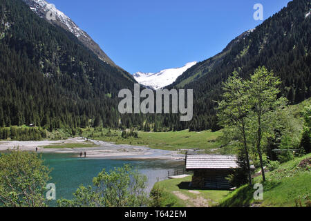 view over a mountain lake at Finkau near Gerlos with fishermen fishing and Mt. Gabler at Zillertal alps in springtime, Tyrol, Austria - Stock Photo