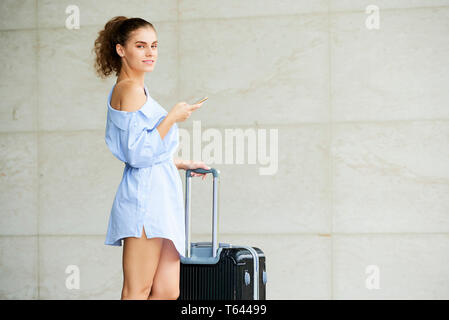 Pretty young woman with luggage - Stock Photo