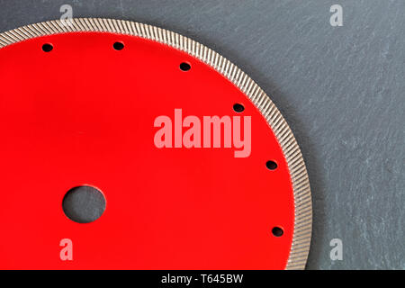 Part of a diamond red disc for cutting against a gray granite background close-up. - Stock Photo