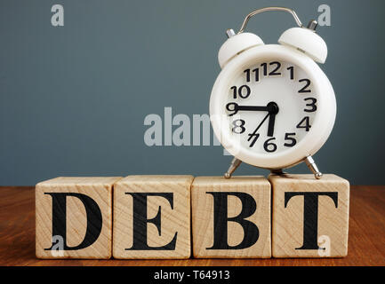 Time to pay debt. Alarm clock and cubes. - Stock Photo