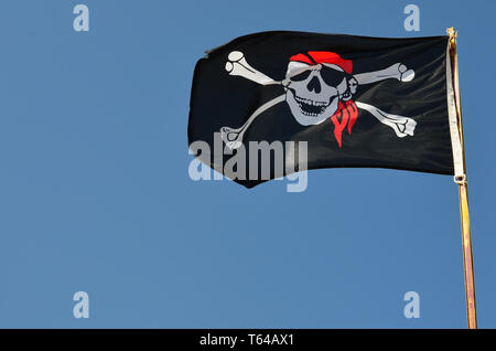 Pirate flag against clear,  blue sky fluttering in the wind, copy space - Stock Photo