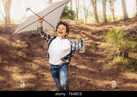 Cheerful boy running downhill with a kite in hand. Happy boy flying a kite in forest.