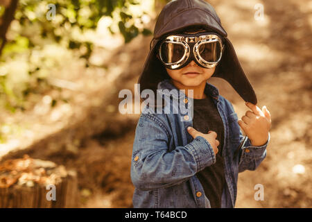 Cute boy with pilot goggles and hat. Kid dreaming to be pilot playing in forest.