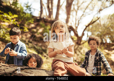 Cute girl sitting on a log with sticks in hand and her friends around in forest. Boys and a girl playing in forest. - Stock Photo