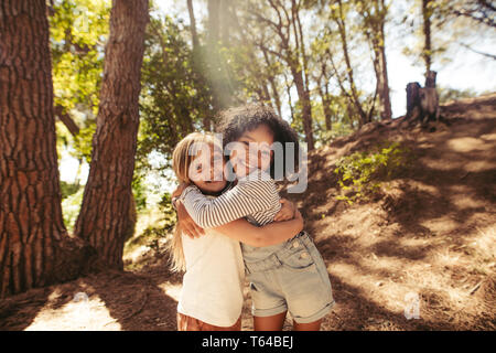 Two girls hugging each other outdoors. Kids together in forest having a great time.
