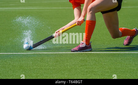 Female field hockey player passing to a team mate on a modern, water artificial astroturf field - Stock Photo