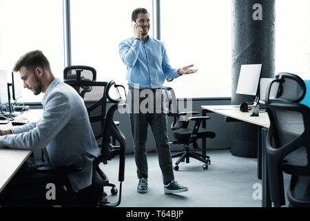 Business man standing inside office building and using cell phone. - Stock Photo