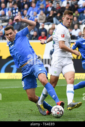 Hoffenheim, Germany. 28th Apr, 2019. Adam Szalai (L) of Hoffenheim vies with Robin Knoche of Wolfsburg during the Bundesliga match between VfL Wolfsburg and TSG 1899 Hoffenheim in Hoffenheim, Germany, April 28, 2019. Wolfsburg won 4-1. Credit: Ulrich Hufnagel/Xinhua/Alamy Live News - Stock Photo