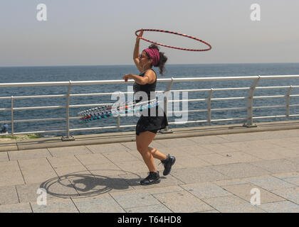 Beirut, Lebanon. 29th Apr, 2019. A woman twirling hoops on Beirut Raouche seafront promenade on a hot and humid spring day in the Lebanese Capital as temperatures reach 26 degrees celsius Credit: amer ghazzal/Alamy Live News - Stock Photo