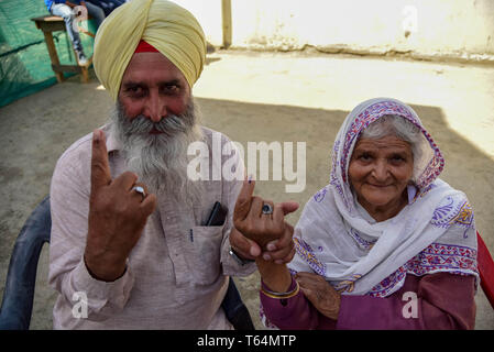 Kulgam, Jammu and Kashmir, India. 29th Apr, 2019. Kashmiri voters are seen showing off their inked fingers after casting their votes outside a polling station in Kulgam, South of Srinagar.On the fourth phase of India's Parliamentary elections, Indians went to polls to cast their ballots amid complete shutdown and internet gag. Credit: Idrees Abbas/SOPA Images/ZUMA Wire/Alamy Live News - Stock Photo