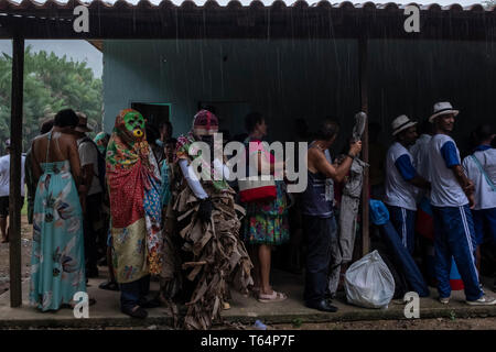 29 April 2019, Brazil, Cariacica: Members of music groups, masked people and visitors stand briefly under one roof in the rain as part of the 'carnaval de gongo de Roda D'Agua'. The folk festival originated 100 years ago in the culture of slaves. According to oral tales, the slaves used to celebrate because they were not allowed to participate in the feast in honour of the Virgin of the Penha. Many of them, who did not want to be recognized, wore masks. Others even covered themselves with straw or dry leaves from the banana tree. Thus the fantasy figure 'Joao Bannaneira' (Hans Bananengewächs) - Stock Photo