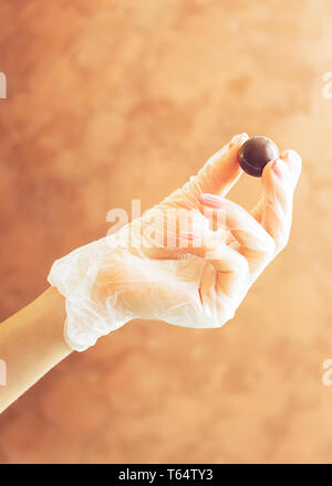Female gloved hand holding a round chocolate candy. Making handmade chocolates. Minimalism. Vertical frame. - Stock Photo