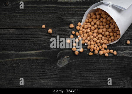 The dry chickpeas on dark wooden desk board. Cicer arietinum. Legume of the family Fabaceae. Egyptian pea - Stock Photo