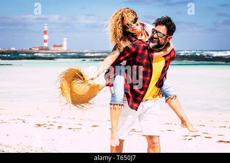 Cheerful people happy joyful couple playing together in love with man carrying woman laughing a lot having fun at the beach in summer holiday vacation - Stock Photo
