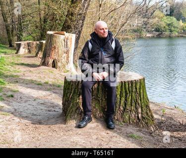 Berlin,Pankow. Weissensee State park, White Lake public park with Elderly senior man sitting on tree stump