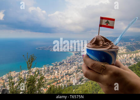 Enjoy beautiful Lebanon   Female hand holding ice cream with Lebanese flag with view of the city of Harissa